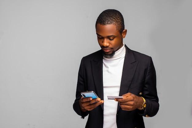 흥분한 아프리카계 미국인 남자는 온라인 쇼핑을 위해 스마트폰과 신용 카드를 사용하고 있고, 행복한 흑인 남자는 온라인으로 음식을 주문하고, 남성은 오랫동안 기다려온 휴대폰 구매 비용을 지불하고 있습니다. 전자금융