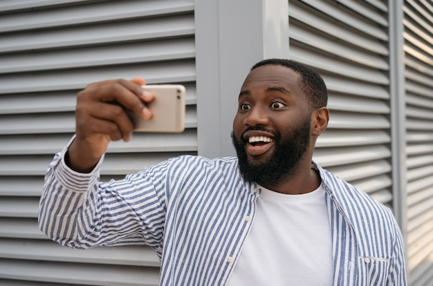 Excited african american man taking selfie using mobile phone standing on urban street. emotional blogger influencer shooting video