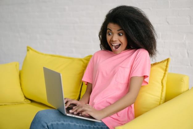 ラップトップコンピューターと高速インターネット接続を使用して、ソファーに座って、映画を見て興奮したアフリカ系アメリカ人の女性。感情的な顔のオンラインショッピング、注文食品と美しい巻き毛の髪の女の子
