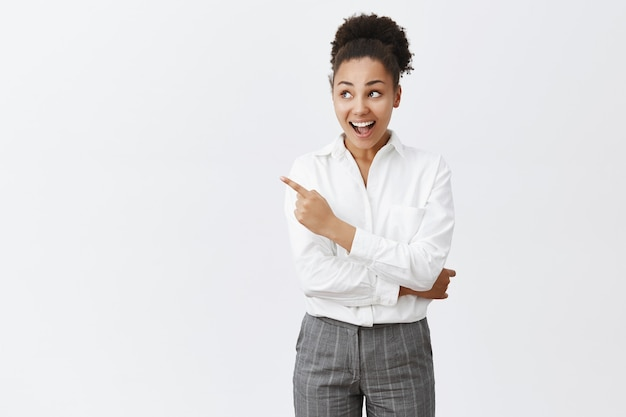 Excited african-american woman in white shirt, looking and pointing upper left amazed