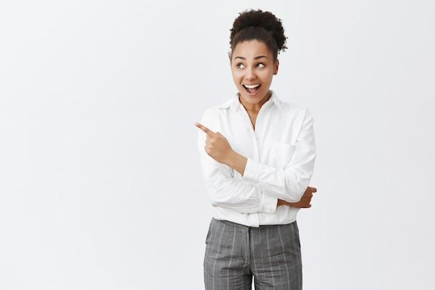 Eccitata donna afro-americana in camicia bianca, guardando e indicando in alto a sinistra stupita