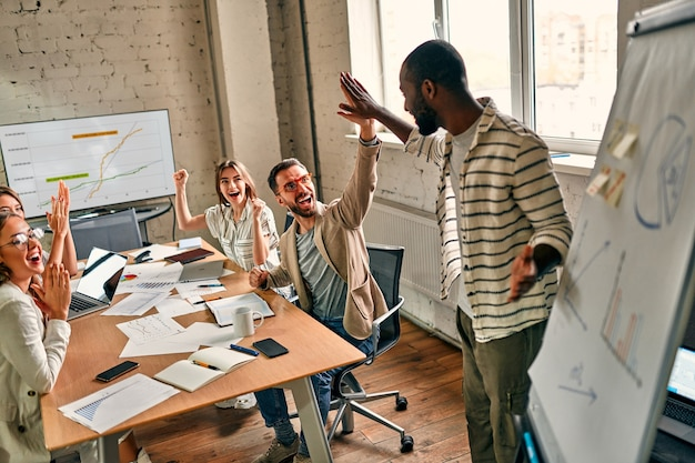 Взволнованная бизнес-команда из африки и кавказа, мотивированная победой, достижением или хорошей работой