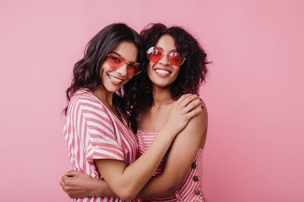 親友を抱きしめる丸いサングラスで興奮したアフリカの女性モデル。楽しんでいる陽気な黒人若い女性の屋内写真