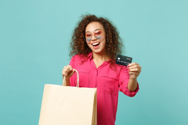 Excited african girl in heart sunglasses hold package bag with purchases after shopping credit card isolated on blue turquoise background. people sincere emotion lifestyle concept. mock up copy space.