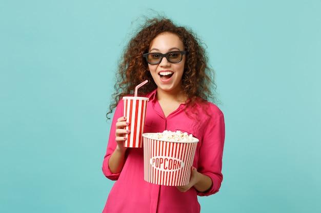 3d 아이맥스 안경을 쓴 흥분한 아프리카 소녀가 스튜디오에서 파란색 청록색 배경에 격리된 팝콘 음료수 한 컵을 들고 영화 영화를 보고 있습니다. 영화, 라이프 스타일 개념에서 사람들의 감정. 복사 공간을 비웃습니다.