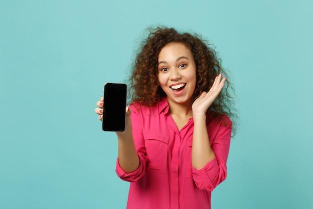 カジュアルな服装で興奮したアフリカの女の子は、スタジオの青いターコイズブルーの壁の背景に分離された空白の空の画面で携帯電話を保持します。人々の誠実な感情、ライフスタイルのコンセプト。コピースペースをモックアップします。