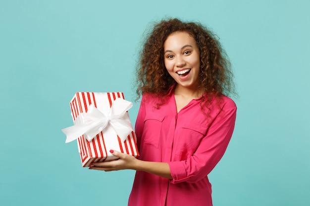 カジュアルな服装で興奮したアフリカの女の子は、青いターコイズブルーの壁の背景に分離されたギフトリボンと赤い縞模様のプレゼントボックスを保持します。国際女性の日の誕生日の休日の概念。コピースペースをモックアップします。