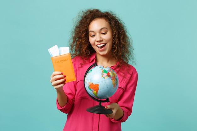 地球の世界の地球儀、パスポート、搭乗券のチケットを保持しているカジュアルな服を着て、青いターコイズブルーの背景で隔離の興奮したアフリカの女の子。人々の誠実な感情、ライフスタイルのコンセプト。コピースペースをモックアップします。