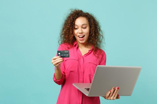 スタジオで青いターコイズブルーの背景に分離されたクレジットバンクカードを保持しているラップトップpcコンピューターを使用してカジュアルな服装で興奮したアフリカの女の子。人々の誠実な感情のライフスタイルの概念。コピースペースをモックアップします。