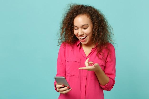 분홍색 캐주얼 옷을 입은 흥분한 아프리카 소녀는 휴대폰을 사용하여 스튜디오의 파란색 청록색 벽 배경에 격리된 sms 메시지를 입력합니다. 사람들은 진심 어린 감정, 라이프 스타일 개념입니다. 복사 공간을 비웃습니다.