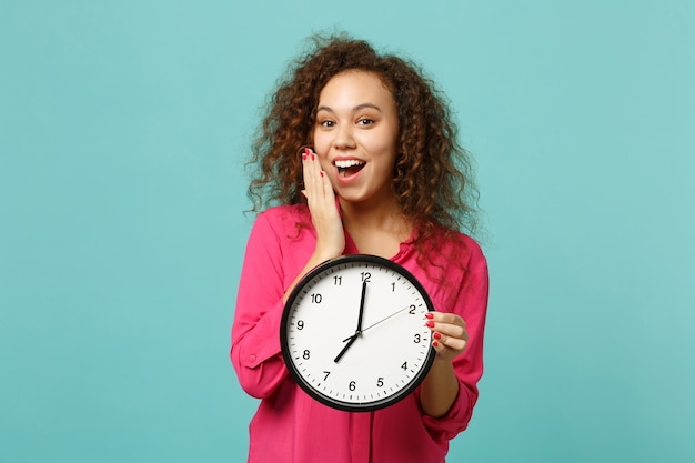 Excited african girl in pink casual clothes covering mouth with hand, hold round clock isolated on blue turquoise background in studio. people sincere emotions, lifestyle concept. mock up copy space.
