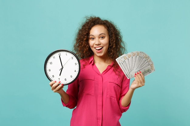 Excited african girl in pink clothes hold round clock fan of money in dollar banknotes cash money isolated on blue turquoise background. people sincere emotions, lifestyle concept. mock up copy space.