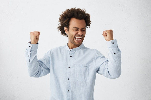 Excited african male winner raising his fists with great happiness having good mood