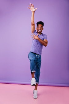 Excited african model in white shoes dancing. indoor shot of carefree brunette man wears purple t-shirt.