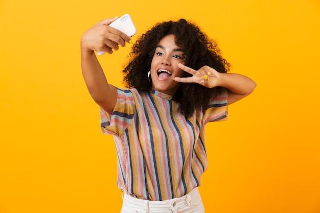 黄色い空間に孤立してポーズをとる興奮したアフリカの女性は、平和のジェスチャーを示す携帯電話で自分撮りを取ります。