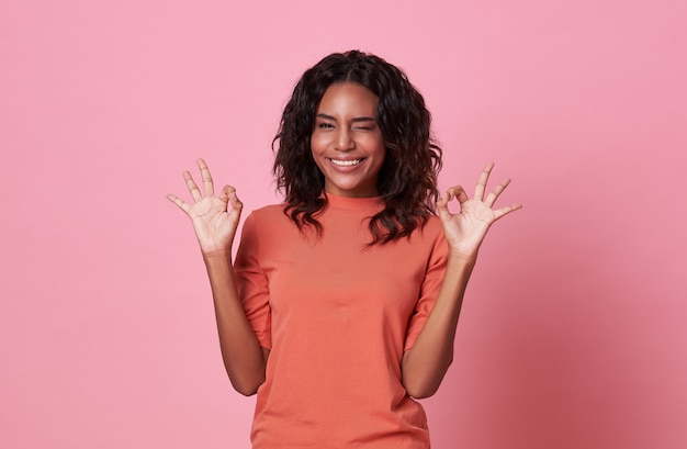 Excited african woman showing ok gesture, looking at camera wearing casual orange t-shirt