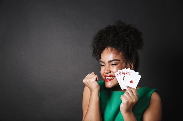 검은 공간 위에 고립 된 카드 놀이를 보여주는 드레스를 입고 흥분된 아프리카 여자