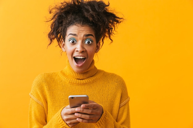 Excited african woman wearing sweater standing isolated, holding mobile phone