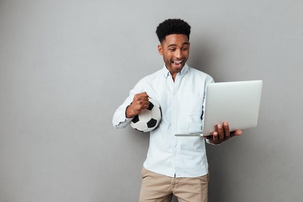ラップトップコンピューターの画面を見て興奮しているアフロアメリカンの男