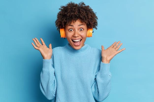 흥분된 아프리카 계 미국인 여성이 실내에서 재미를 느끼고 손바닥을 들고 스테레오 헤드폰을 통해 좋아하는 음악을 즐겁게 들으며 캐주얼 한 스웨터 포즈를 취합니다.