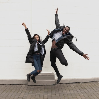Excited afroamerican couple jumping full shot