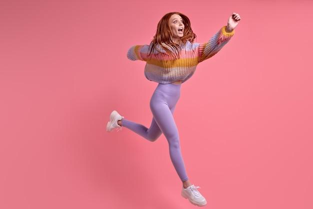 ピンクのスタジオの背景の上に分離されたカジュアルな服を着て、販売割引後の興奮した驚いた女性のジャンプランはすごいomg表現を叫び、白人女性は急いで