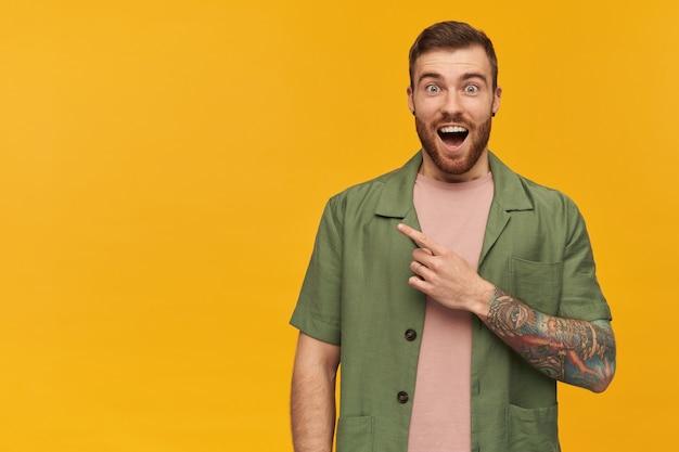 갈색 머리와 수염을 가진 흥분되고 놀란 남자. 녹색 반팔 재킷을 입고. 문신이 있습니다. 노란색 벽 위에 고립 된 복사 공간에서 왼쪽을 가리키는 손가락