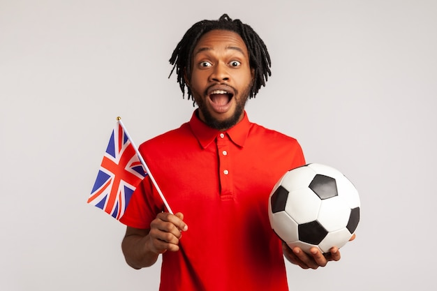 Excited amazed man holding british flag and soccer black and white ball, united football league.