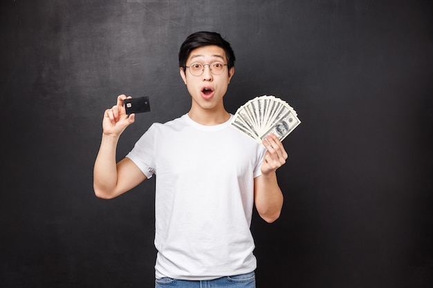 Excited and amazed rich lucky asian guy holding dollars and credit card with astonished expression