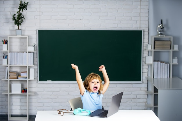 학교 수업 시간에 노트북 컴퓨터를 들고 흥분한 놀란 학생입니다.