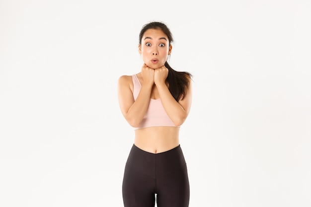 Excited and amazed, thrilled asian fitness girl in activewear looking at discount banner, special offer advertisement, standing