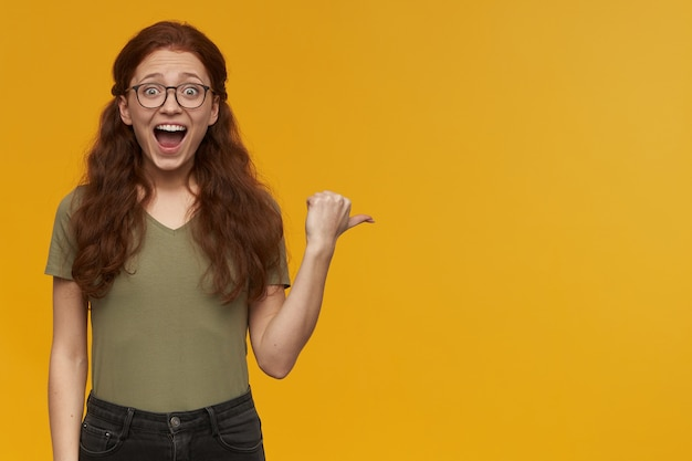 Excited, amazed woman with long ginger hair. wearing green t-shirt and glasses. pointing with thumb to the right at copy space, isolated over orange wall