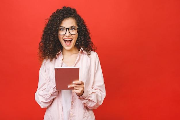 Возбужденная удивленная молодая красивая женщина с планшетным пк