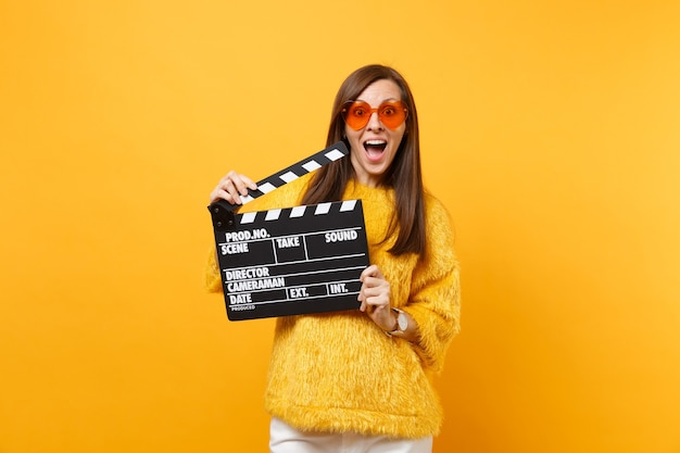 毛皮のセーター、黄色の背景に分離されたカチンコを作る古典的な黒のフィルムを保持しているオレンジ色のハートの眼鏡で興奮して驚いた若い女性。人々は誠実な感情、ライフスタイル。広告エリア。