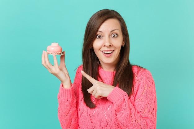 Возбужденная изумленная молодая женщина в вязаном розовом свитере, указывая указательным пальцем на торт в руке, изолированной на синем бирюзовом стенном фоне, студийный портрет. концепция образа жизни людей. копируйте пространство для копирования.