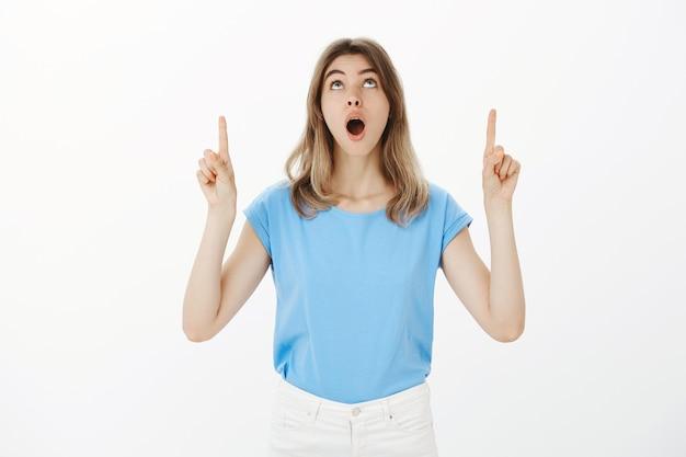 La donna bionda eccitata e divertita si chiese a bocca aperta, puntando le dita verso l'alto