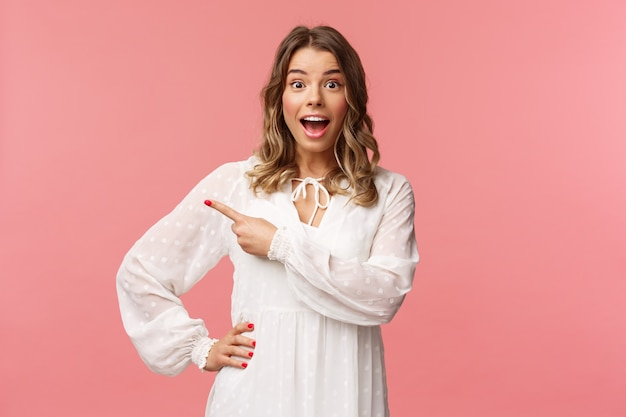 Excited and amused, intrigued blond european girl in white cute spring dress, open mouth wondered and amazed of hearing awesome news, pointing finger left at something cool, on a pink wall