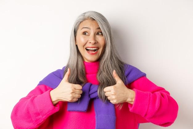 興奮して驚いたアジアの年配の女性は、承認で親指を立て、左上隅で幸せに笑って、何か素晴らしい、白い背景を賞賛している