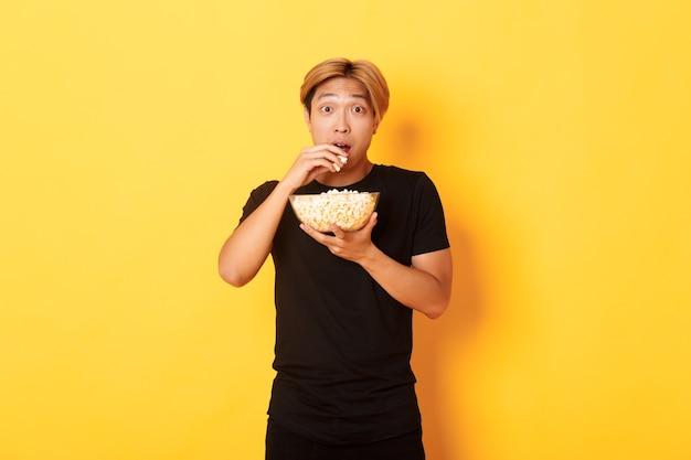 재미있는 영화를보고 그릇에서 팝콘을 먹고, 노란색 벽에 서서 흥분하고 놀란 아시아 사람.