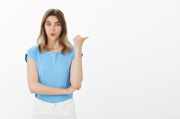 興奮して驚いた金髪の女性が親指を右に向け、発表を示している