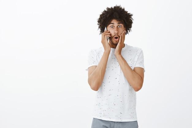 携帯電話で話している興奮して驚いた浅黒い肌の男、衝撃的なニュースを聞く