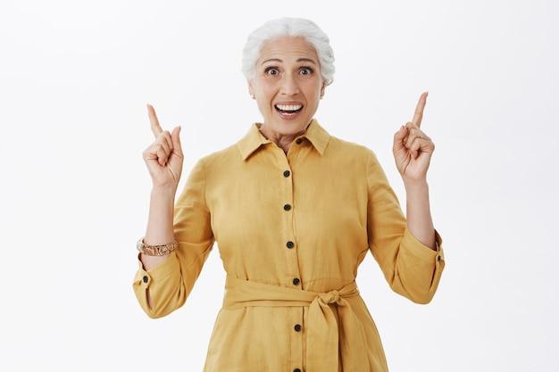 Взволнованная и удивленная улыбающаяся старушка, указывая пальцами вверх, на белом фоне