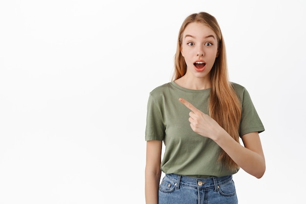 Возбужденная и любопытная девушка с открытым ртом показывает влево, демонстрирует потрясающую новую промо-сделку, баннер магазина на copyspace, стоит над белой стеной