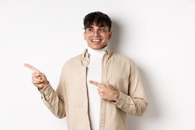 眼鏡をかけ、指を指して、幸せな笑顔で左を見て、白い背景に畏敬の念を抱いて立っている興奮して熱狂的な若い男