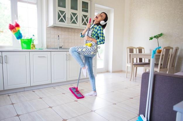 エプロンで興奮して幸せな美しい若い女性が自宅のキッチンの床を掃除して踊っています