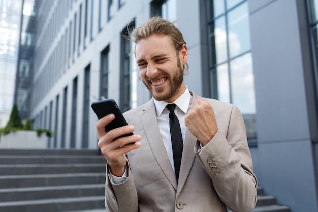 흥분되고 행복한 사업가 우승자는 승리에서 행복감에 스마트폰을 들고 있습니다. 비즈니스 센터 배경에 흰색 셔츠를 입은 곱슬머리 젊은 사업가 관리자의 초상화.