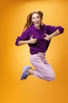 紫色のセーターを着た興奮した幸せな若い赤毛の女性が幸せと満足からジャンプし、承認の親指を立てるジェスチャーを示し、肯定的な返信を与え、素晴らしい服が好きです