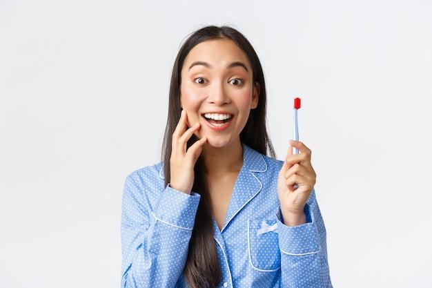 青いパジャマを着た興奮して幸せなゴージャスなアジアの女の子は、歯ブラシを持ってカメラに向かって微笑んでいる白い歯に驚いて満足しているように見え、完璧な歯磨き粉、白い背景を見つけました。