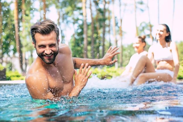 Взволнованная и счастливая современная красивая семья веселится в бассейне во время летних каникул.