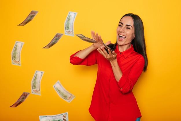 彼女は黄色の壁の背景にポーズをとっている間興奮して幸せな成功した美しい女性はたくさんのお金を楽しんでいます